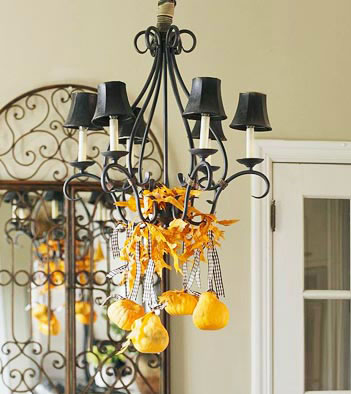 pumpkins hanging from chandlier with ribbon