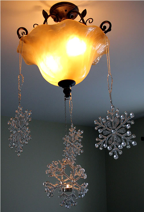 hanging snowflake ornaments from light fixture